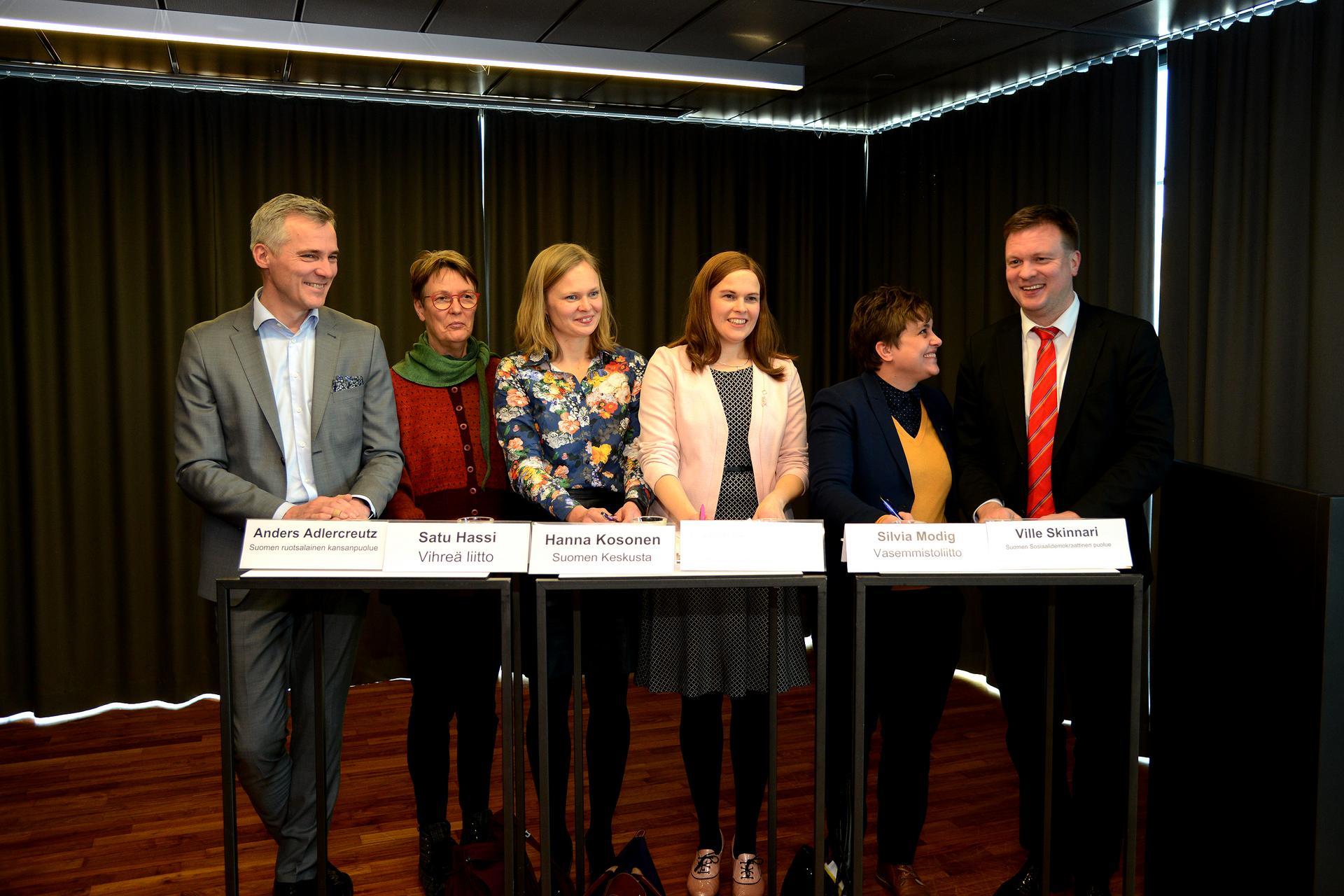 Kuuden puolueen kansanedustajat seisovat yhtenä rivinä valmiina vastaamaan tiukkoihin kysymyksiin Itämerestä